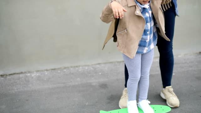 mama lehrt töchter zum skateboard - fürsorglichkeit stock-videos und b-roll-filmmaterial