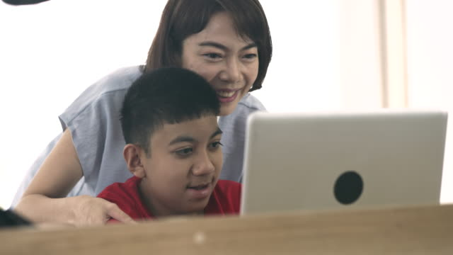 mom teaching her disabled boy using laptop at home - 10 11 years stock videos & royalty-free footage