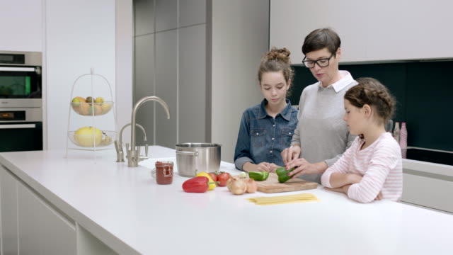 mom teaching kids to cook a meal - arbeitsplatte stock-videos und b-roll-filmmaterial