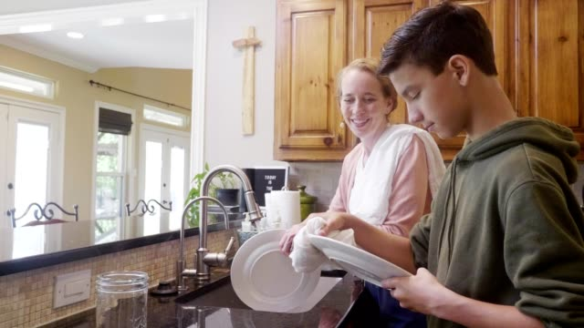 mom washes dishes with preteen son - drying stock videos & royalty-free footage