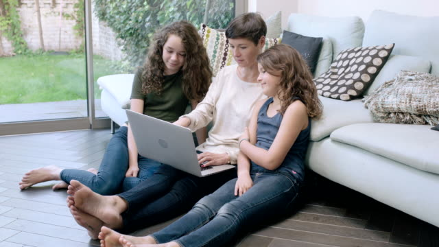 mom with daughters using laptop together - little girls bare feet stock videos and b-roll footage