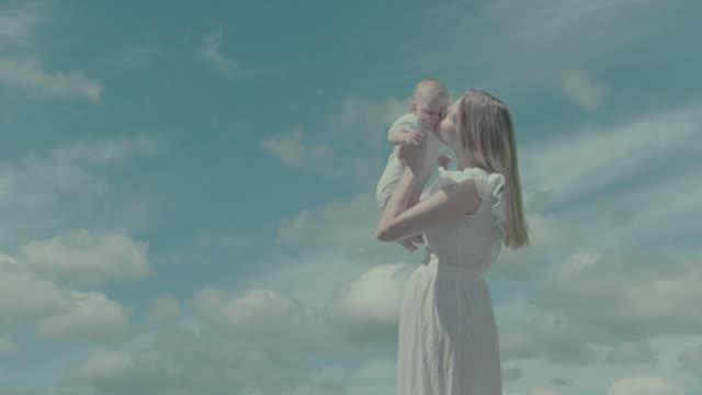空の背景で幼い息子を持つお母さん - モンタージュ点の映像素材/bロール
