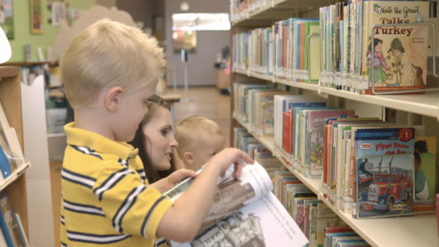 ms mom with two little boys browsing childrens books at public library / rancho mirage, california, usa - rancho mirage stock videos & royalty-free footage
