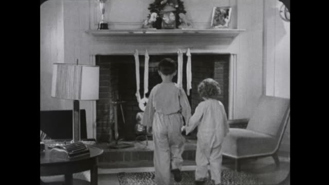 1939 moments of christmas eve, decorated trees, excited children, snow and santa - リース点の映像素材/bロール