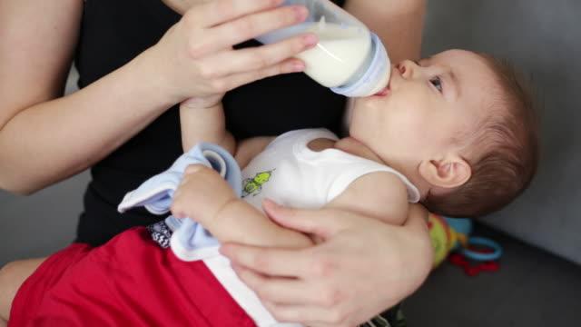 mommy bottle feeding the baby boy - feeding stock videos & royalty-free footage