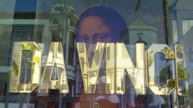 vídeos de stock, filmes e b-roll de mona lisa painting by leonardo da vinci on electronic digital advertising fashion window display at the luxurious boutique store on rodeo drive in beverly hills, los angeles, california, 4k - capital letter