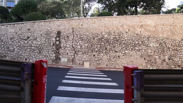 monaco grand prix barriers, a zebra crossing and cars driving past in front of a stone wall - monaco stock videos and b-roll footage