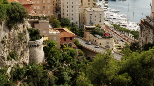 monaco – rock face, residential houses and street - port hercules in background - spoonfilm stock-videos und b-roll-filmmaterial