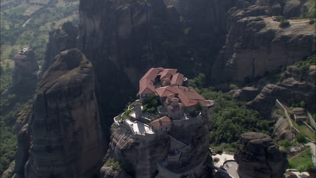 A monastery built on a rock formation towers above a valley.