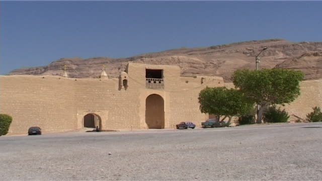 vídeos de stock, filmes e b-roll de monastery of st anthony ws of the exterior of the monastery with the red sea mountains behind built in 300 ce the monastery of st anthony is the... - arcaico