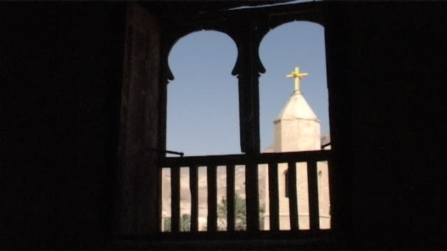 vidéos et rushes de monastery of st anthony view of a bell tower with a cross from a balcony with framed arched openings built in 300 ce the monastery is the oldest in... - flèche clocher