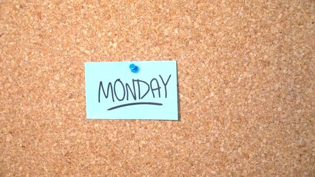 紙の男がコルクボードに固定を月曜日の単語 - ペンテコステ点の映像素材/bロール