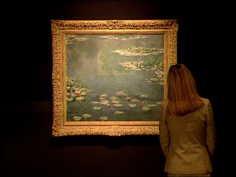 vídeos y material grabado en eventos de stock de monet painting displayed for first time in 80 years; itn england: london: int sequence woman looking at monet painting of water lillies which has... - nenúfar