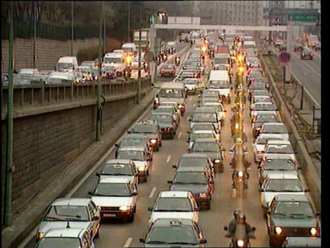 EU Monetary Union EU Monetary Union Paris TGV Solid traffic jam of three lanes MS Young girl and man trying to hitchhike TX as he holds sign 'Saclay'...