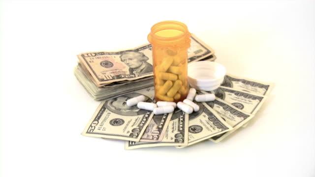 denaro e medicina. spese mediche. denaro, contanti, farmaci, pillole. - banconota da 10 dollari statunitensi video stock e b–roll