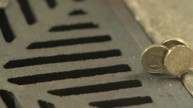 Money Down the Drain - High speed 3 English one pound coins rolling in to road drain, cu