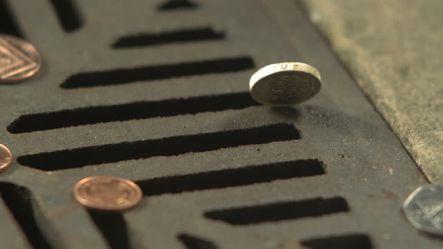 money down the drain - high speed english one pound coin falls, spins and disappears in to road drain, cu - geldmünze stock-videos und b-roll-filmmaterial