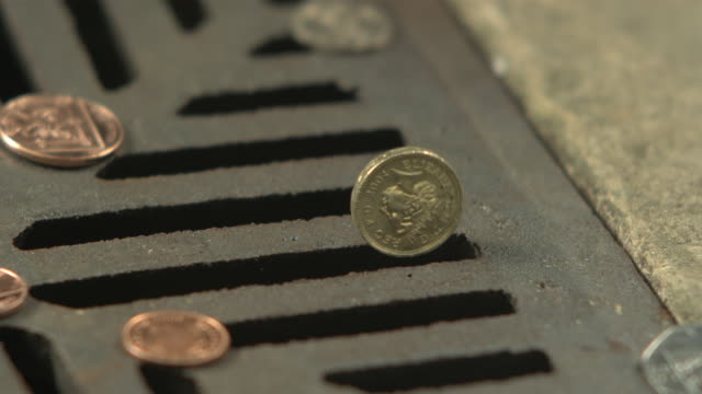 Money Down the Drain - High speed English one pound coin spins and disappears in to road drain, cu
