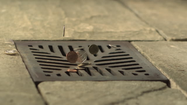vidéos et rushes de money down the drain - high speed various english coins falling on and in to road drain, wide - bonde