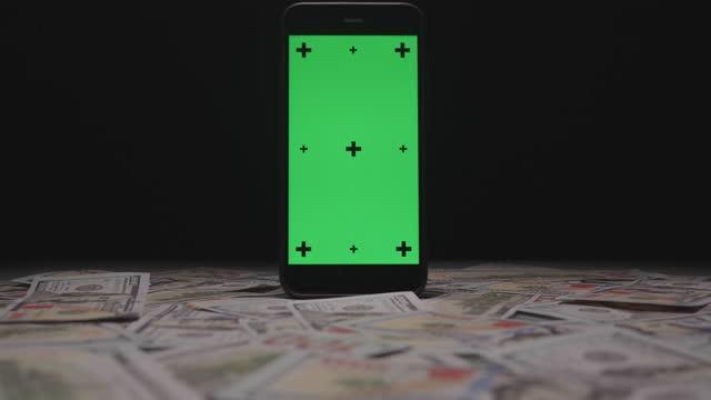 緑の画面でスマートフォンの近くに落ちるお金 - ペア点の映像素材/bロール