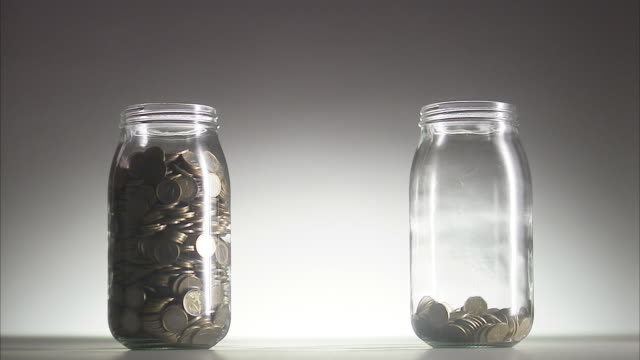 money in jars. - contrasts stock videos and b-roll footage