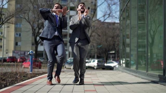 vidéos et rushes de argent faisant des hommes d'affaires dansant tout en acclamant dans la rue - collègue