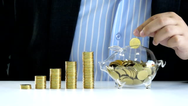 Money Saving, Business, Banking, Investment, Financial and Life Insurance concept - Slow Motion young businessman drop golden coin into piggy bank glass for saving money to investment in future business plan and financial life