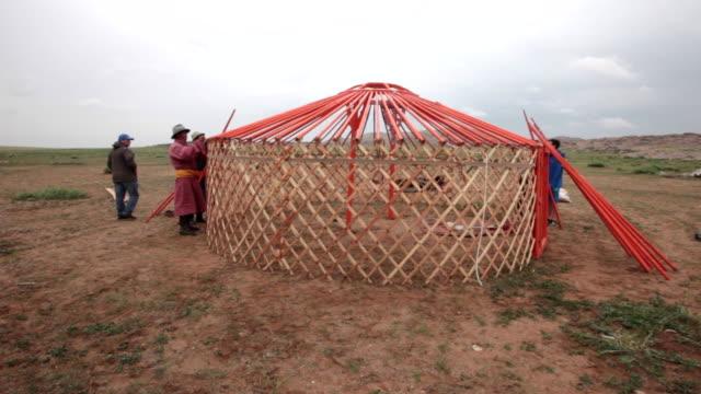 Mongolians in traditional clothing (Deel) building a yurt in Gobi desert, Mongolia