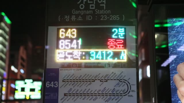 a monitor displays the estimated arrival times of buses at a bus stop as a bus arrives and passengers climb aboard at gangnam station in seoul south... - boy band stock videos & royalty-free footage