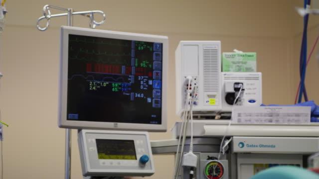 stockvideo's en b-roll-footage met ekg monitor during a surgical procedure in a hospital operating room. - dokterspraktijk