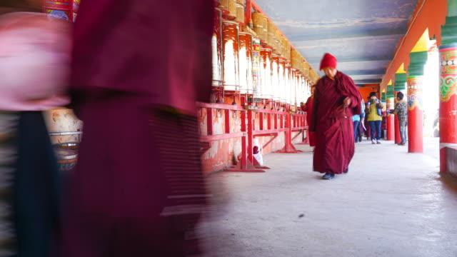 monaco e suora un piedi tutto ruota di preghiera in larung gar (larung cinque sciences monaci academy). il famoso monastero, al seda, sichuan, cina. - lama oggetto creato dall'uomo video stock e b–roll