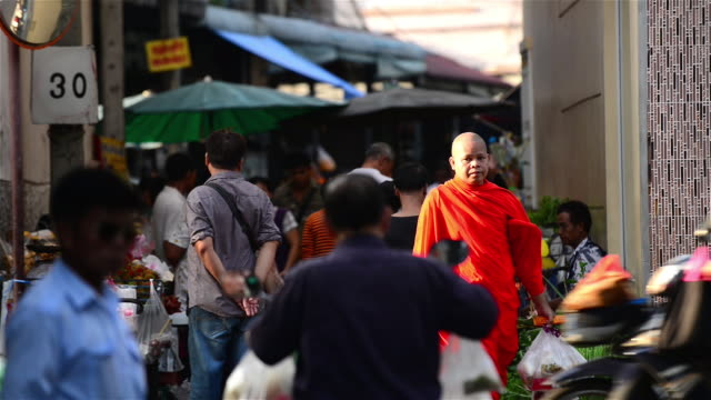a monk crossing the street while taking alm during morning hours of bangkok - alm stock-videos und b-roll-filmmaterial