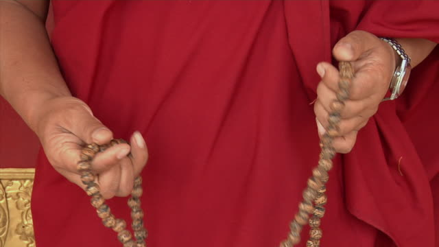 cu, zo, monk holding prayer beads at tibetan monastery, mid section, bodh gaya, bihar, india - prayer beads stock videos & royalty-free footage