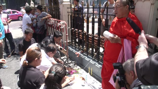 monk leads a prayer at erawan shrine after it reopened two days after a bomb exploded close to the shrine in the center of thailand's capital,... - エラワン聖堂点の映像素材/bロール