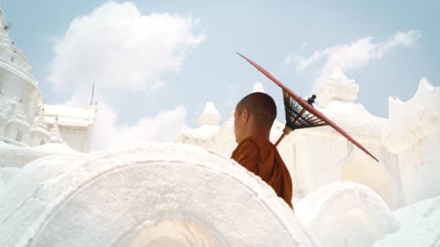 monk make a merit with umbrella - bagan stock videos & royalty-free footage