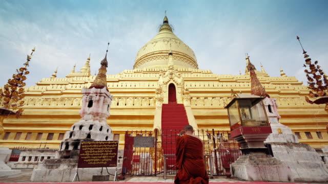 monk make merrit at gloden shwezigon pagoda - temple building stock videos & royalty-free footage