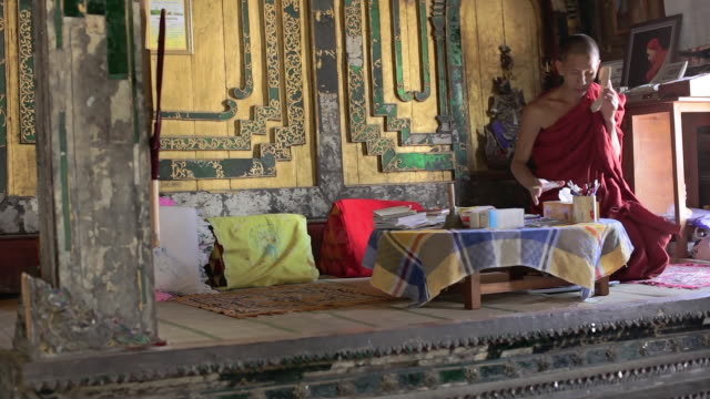 ws monk on phone in his office, taking notes / inle lake, shan state, myanmar  - shan state stock videos & royalty-free footage