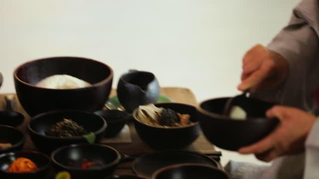 monk putting rice within food for offering to buddha in bowl at baegyangsa temple in naejangsan mountain / jangseong-gun, jeollanam-do, south korea - 韓国文化点の映像素材/bロール