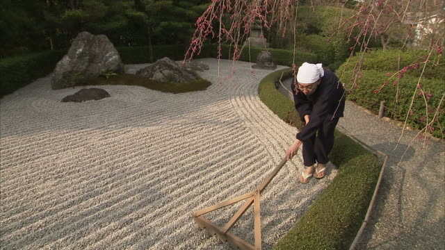 ms pan monk raking rock garden at taizohin temple, kyoto, japan - formal garden stock-videos und b-roll-filmmaterial