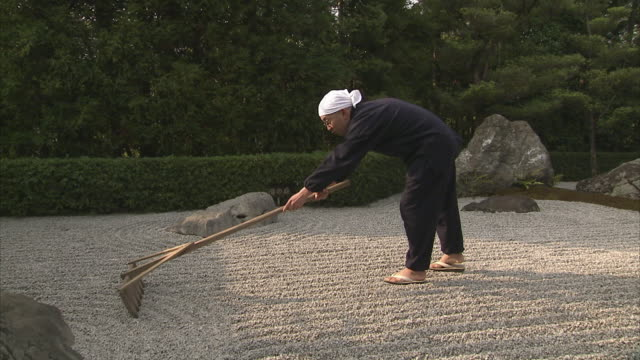 ws pan monk raking rock garden at taizohin temple, kyoto, japan - buddhismus stock-videos und b-roll-filmmaterial