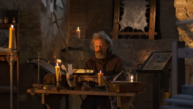 hd: monk reading by candlelight - medieval stock videos & royalty-free footage