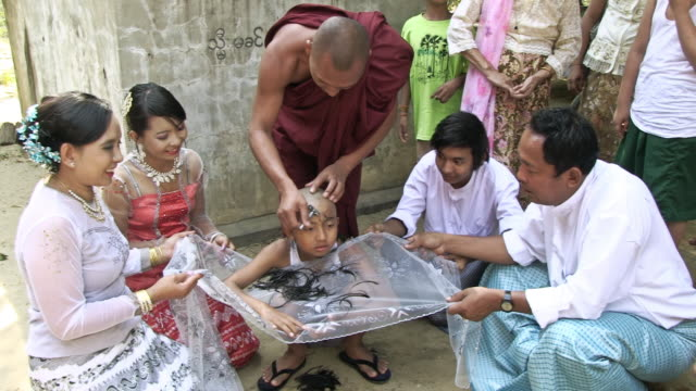 ws monk shaving a boy's head, boy's hair is falling into a beautiful cloth other men and women are holding / bagan, mandalay division, myanmar - mandalay stock videos and b-roll footage