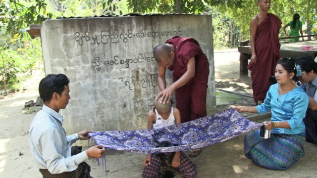 WS monk shaving a boy's head, Boy's hair is falling into a beautiful cloth a man and a woman are holding / Bagan, Mandalay Division, Myanmar