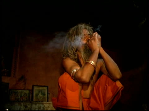MS monk smoking in dark room, Rajasthan, India
