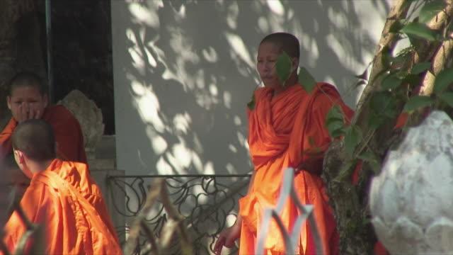 vídeos de stock e filmes b-roll de ms monk smoking outside temple, luang prabang, laos - fotografia de três quartos