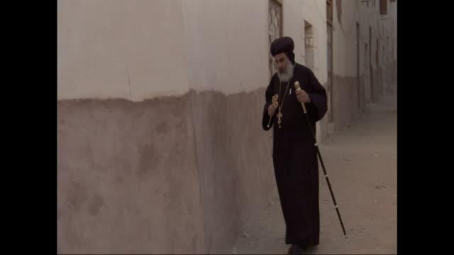 vidéos et rushes de a monk uses an ornate staff as he hurries down a narrow street. - christianisme