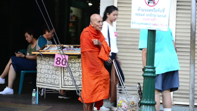 a monk walking along footpath while taking alm during morning hours of bangkok - alm stock-videos und b-roll-filmmaterial