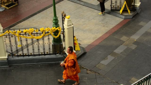 a monk walking along the street on bangko taking alm - alm stock-videos und b-roll-filmmaterial