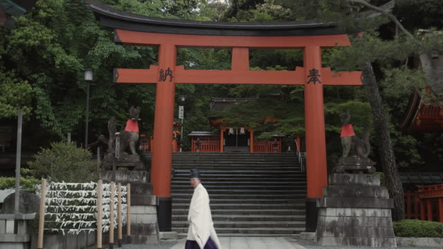 ws monk walking in front of torii gate flanked by stone statues of foxes (kitsune) at fushimi inari taisha shrine, kyoto, japan - 日本語の文字点の映像素材/bロール