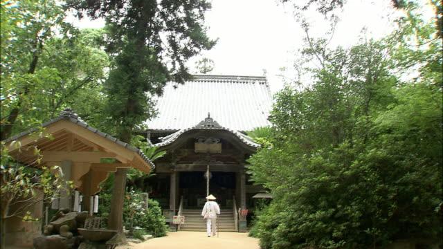 vídeos de stock, filmes e b-roll de a monk walks into the joruri-ji temple. - templo
